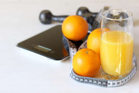 Orange fruits, juice and a centimeter against the background of weights and dumbbells. diet and exercise for health Zdjęcie Seryjne