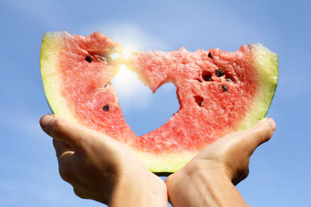 slice of ripe watermelon in hands raised to the sky. favorite hot sweet summer