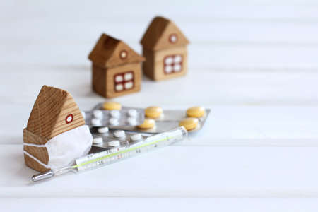wooden house in an individual mask with a thermometer and tablets against the background of other houses. self-isolation with viral infections Disease
