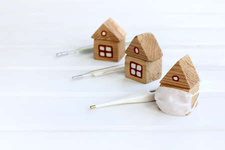 houses with thermometers, one of which is in a medical mask. symptom testing and self-isolation