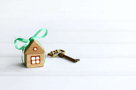house with a green bow and golden key on a light background with copy space. new luxury home as a gift Zdjęcie Seryjne