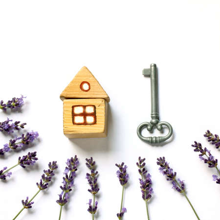 wooden house and metal key with sprigs of lavender. individual accommodation with a plot