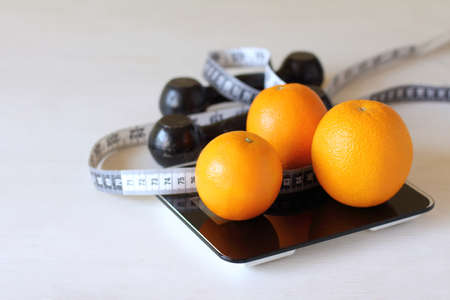 oranges, a centimeter ruler and dumbbells on the scales. fruits and exercise for health
