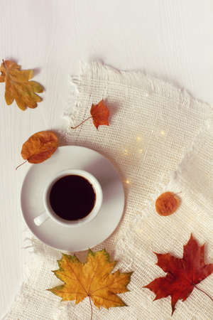 black coffee in a white cup surrounded by autumn leaves on the table top view. warming atmosphere for a break