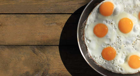 cast iron skillet with many fried chicken eggs on a wooden table top view. a large dish with a rustic scrambled eggs