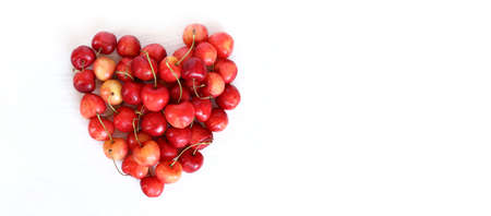 heart from red berries of sweet cherry on a light surface top view. big sweet love