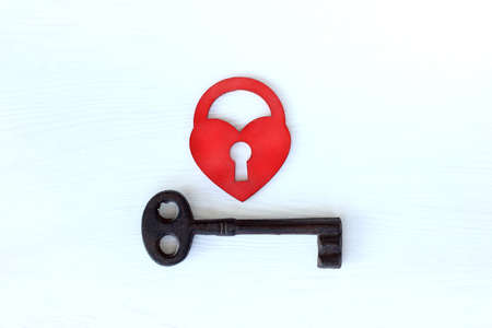 red heart in the form of a lock and a large metal key, top view. love unites different Zdjęcie Seryjne