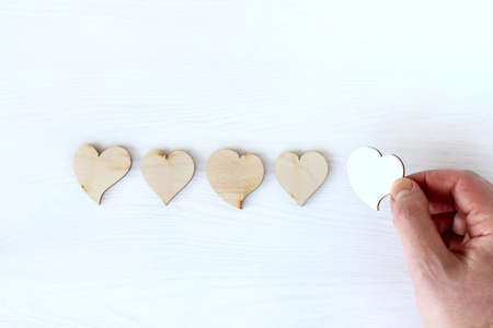hand adds white heart symbol to four wooden ones on table top view. new follower increases rating Zdjęcie Seryjne