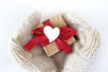 hands in white knitted mittens hold a gift with a red bow decorated with a heart symbol, top view. Congratulations on the Day of lovers