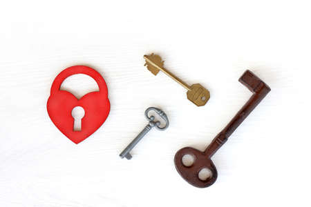 three different keys and red heart in the form of a lock, top view. true love opens
