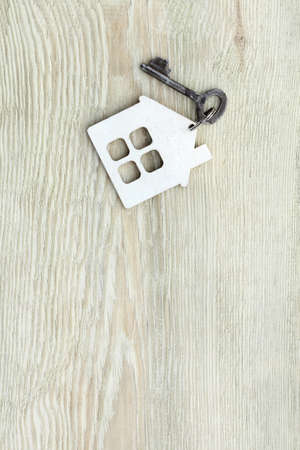 flat lay with keychain from very old house and shabby key on gray-green wooden background top view. secondary housing offer