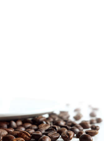 roasted coffee beans on a table close-up on a blurred white background. background for invigorating inscriptions