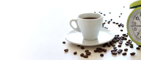 coffee beans and a cup of espresso next to the alarm clock on the table. time for an invigorating drink