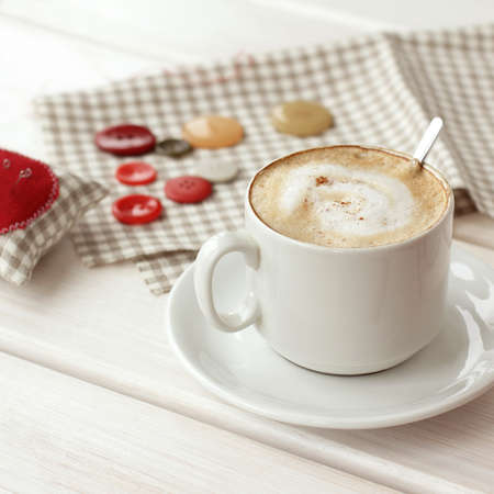 frothy cappuccino in a mug on the background of needlework on the table. home coffee break