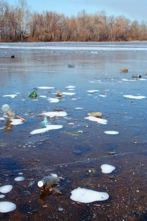 A lot of bottles frozen in river ice cover. River pollution