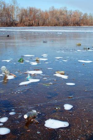 Beaucoup de bouteilles figé dans le fleuve couvert de glace. Pollution de la rivière