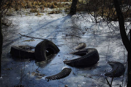 several tires frozen at trench. View of environment pollution Stock Photo - 817679