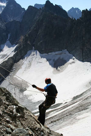 climber descending with rope in his hands photo