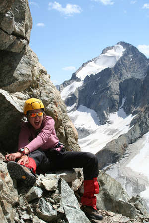 happy girl climber sitting on a rock and smiling photo