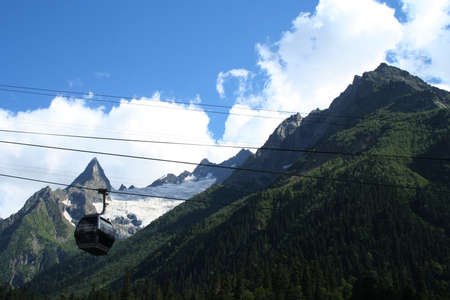 dombai: mountain funicular with rocky peaks of Dombai in the background