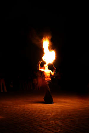 fire-eater performance on a street and audience on a dark background Stock Photo