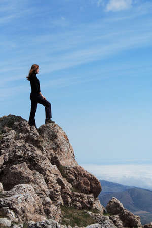 girl standing at the edge of rock photo
