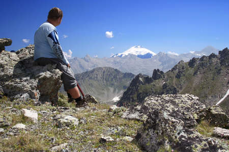 man sitting on a rock and looking at the Elbrus Stock Photo - 1727753