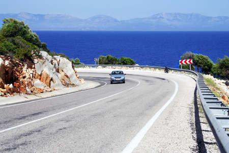 coastline: alone car on a sunny road at sea coastline