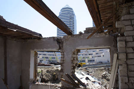 demolished house: modern building through the demolished house window