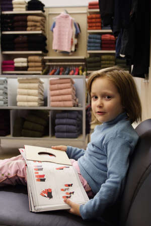 little girl looking through the catalogue at fashion shop Stock Photo - 2262090