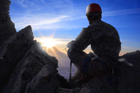 climber sitting on a rock and looking at mountain panorama