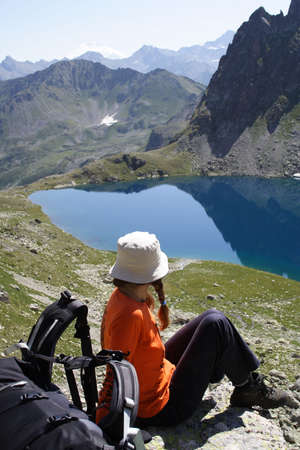girl hiker on a rest looking at big mountain lake Stock Photo - 2262130
