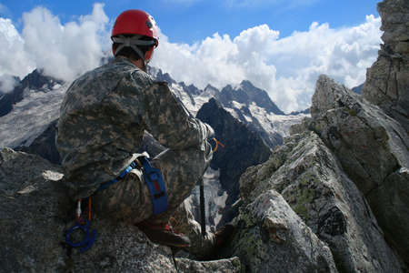 climber sitting on a rock and looking at mountain panorama photo