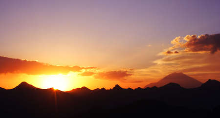 raising sun beams illuminating an Elbrus mountainside