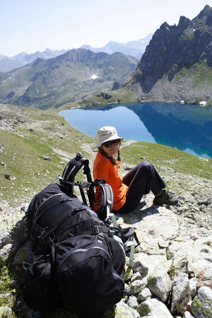 young hiker taking a rest looking at big mountain lake Stock Photo - 2360803