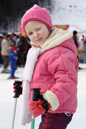 portrait of young girl skier with blurred crowd of skiers at background