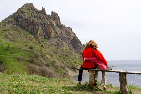 mother and daughter sitting on a bench and looking at the sea photo
