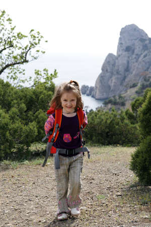 smiling little girl hiker on a path with sea and cliffs on a background Stock Photo