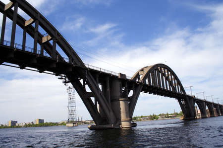 concrete railroad bridge with arches on a river with blue cloudy sky photo