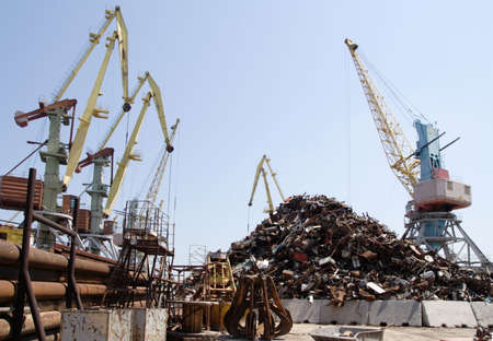 lot of port cranes and heap of scrap metal photo