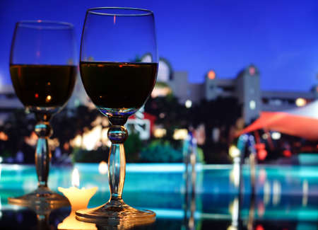 two wineglasses and candle standing on a glass table at the night hotel photo