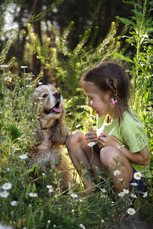 little girl sitting side by side with her dog  photo