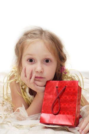 occhi sbarrati: ragazza a palla-abito detiene una confezione regalo. Occhi ben aperti  Archivio Fotografico