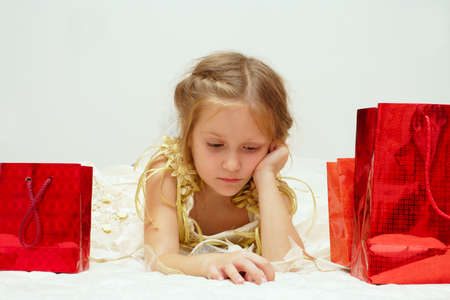 disenchantment: sad girl just received her gifts looking at you  Stock Photo