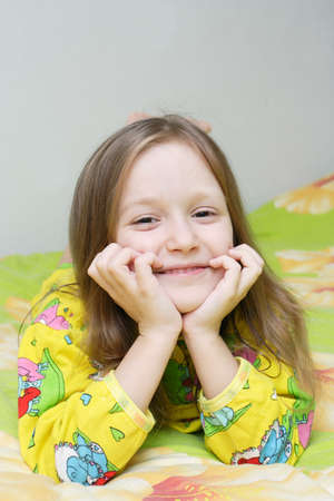smiling little girl lying on a bed  photo