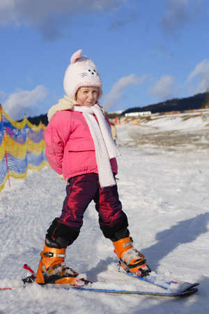 portrait of young girl skier with snowed hill at background