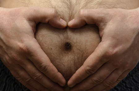 fun pregnancy concept. Man holding a hands like heart shape on his big hairy stomach  photo