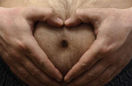 fun grossesse concept. L'homme, comme la tenue d'une main sur son coeur forme hairy big estomac