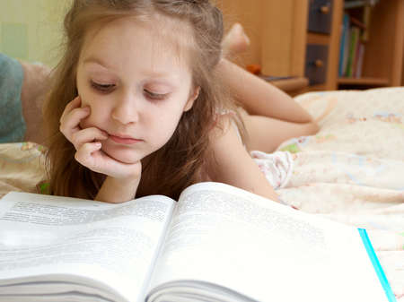 little child girl laying on a bed and reading a book