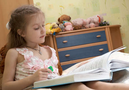 little child girl laying on a bed and reading a book Stock Photo - 4608173